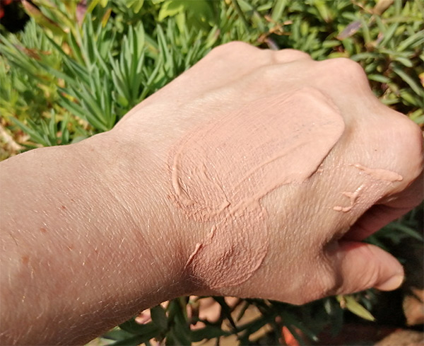 Sukin tinted sunscreen on  the back of the hand